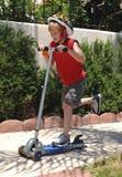 男孩骑马滑行车 免版税库存图片