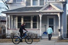 男孩骑马自行车,走入家的妇女 免版税图库摄影