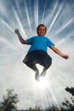 男孩高少许跳 免版税库存照片