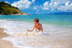 年轻男孩,使用与在海浪的沙子的孩子 库存图片