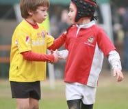 男孩,在8以下变老,有在橄榄球的公平比赛 免版税库存照片