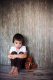 年轻男孩,坐与他的玩具熊的地板,哀伤 库存图片