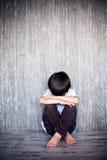 年轻男孩,坐与他的玩具熊的地板,哀伤 图库摄影