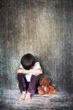 年轻男孩,坐地板,玩具熊在他旁边,哭泣 库存图片