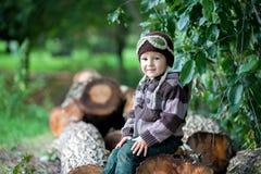 男孩,坐树干 库存照片