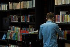 男孩,学生,在书橱工作并且放回书在市政图书馆里 免版税库存图片