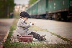男孩,打扮在葡萄酒外套和帽子,带着手提箱 免版税库存照片