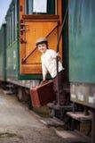 男孩,打扮在葡萄酒衬衣和帽子,带着手提箱 库存图片
