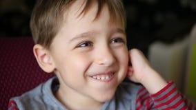 男孩,调查距离,微笑并且握他的在他的耳朵后的手 愉快的孩子显示快乐的情感 股票录像
