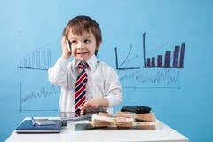年轻男孩,谈话在电话,写笔记、金钱和片剂 免版税图库摄影