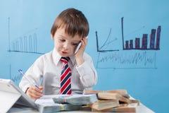 年轻男孩,谈话在电话,写笔记、金钱和片剂 图库摄影