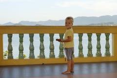 男孩,金发,站立在阳台,看照相机反对山的背景,海 免版税图库摄影