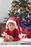 男孩,读在圣诞树前面的一本书 免版税库存图片