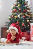 男孩,读在圣诞树前面的一本书 图库摄影