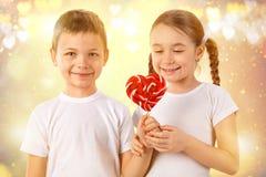 男孩给一个小女孩糖果在心脏形状的红色棒棒糖 日s华伦泰 孩子爱 免版税库存图片
