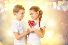 男孩给一个小女孩糖果在心脏形状的红色棒棒糖 日s华伦泰 库存图片