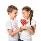 男孩给一个小女孩糖果在白色在心脏形状的红色棒棒糖隔绝的 日s华伦泰 孩子爱 库存图片