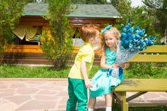 男孩给一朵花一个女孩孩子在生日快乐 庆祝概念和童年,爱 库存照片