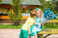男孩给一朵花一个女孩孩子在生日快乐 庆祝概念和童年,爱 库存图片