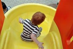 男孩滑下来 免版税图库摄影