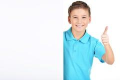 男孩从与赞许姿态的白色横幅看  免版税库存照片