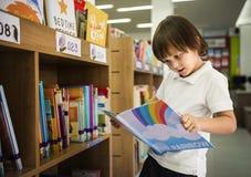 年轻男孩读书儿童故事书在图书馆里 库存图片