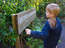 男孩读书动物园标志 免版税库存照片