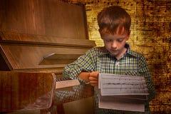 男孩读书钢琴活页乐谱记法的画象 免版税库存图片