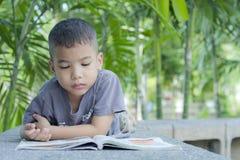 男孩读了一本书。 库存照片