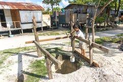 男孩从井的作为水 库存照片