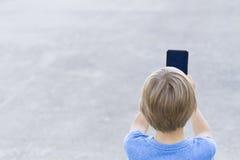 男孩移动电话使用 拍与他的智能手机的孩子照片 灰色都市背景 回到视图 概念查出的技术白色 图库摄影