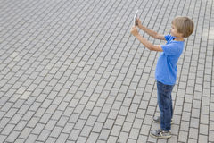男孩移动电话使用 拍与他的智能手机的孩子照片 灰色都市背景 回到视图 概念查出的技术白色 库存照片