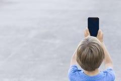 男孩移动电话使用 拍与他的智能手机的孩子照片 灰色都市背景 回到视图 概念查出的技术白色 免版税图库摄影