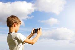 男孩移动电话使用 拍与他的智能手机的孩子照片 背景美丽的天空 回到视图 概念查出的技术白色 图库摄影