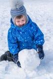 男孩滚动雪球 雪人的一个雪球 免版税库存图片