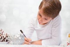 男孩给圣诞老人写一封信 免版税库存图片