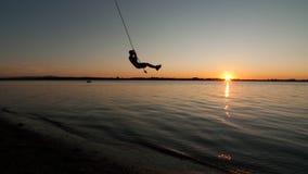 男孩从在尚普兰湖的绳索摇摆在佛蒙特在日落 免版税库存图片