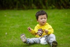 男孩以在草的黄色 库存照片