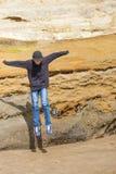 男孩从大砂岩岩石边缘跳 免版税库存照片