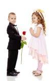 男孩给女孩一朵花 免版税库存照片
