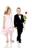 男孩给女孩一朵花 图库摄影