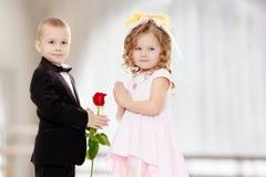 男孩给女孩一朵花 库存照片