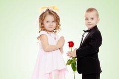 男孩给女孩一朵花 免版税库存图片