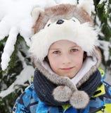 男孩8岁在倒栽跳水的作为在雪背景的一条狗 免版税库存照片