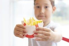 男孩8岁提供在纸箱,快餐的油炸物 库存图片