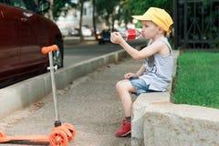 男孩5岁,与在路的一辆滑行车在公园 子项喝水 家庭假日 免版税库存图片