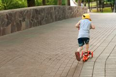 男孩5岁,与在路的一辆滑行车在公园 家庭假日 库存照片