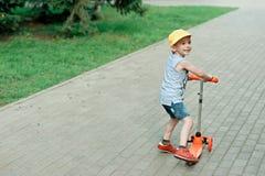 男孩5岁,与在路的一辆滑行车在公园 家庭假日 图库摄影