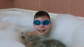 男孩6-7年潜水入泡末浴、神色在照相机和笑 股票视频