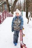 男孩给愉快的冬天穿衣 库存图片